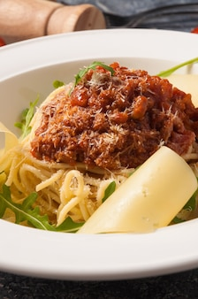 Tasty spaghetti bolognese on a white plate with parmesan and arugula. close up