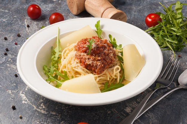 Tasty spaghetti bolognese on a white plate with parmesan and arugula. horizontal frame