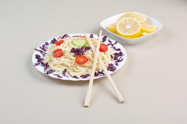 Tasty spaghetti and lemon slices on white surface