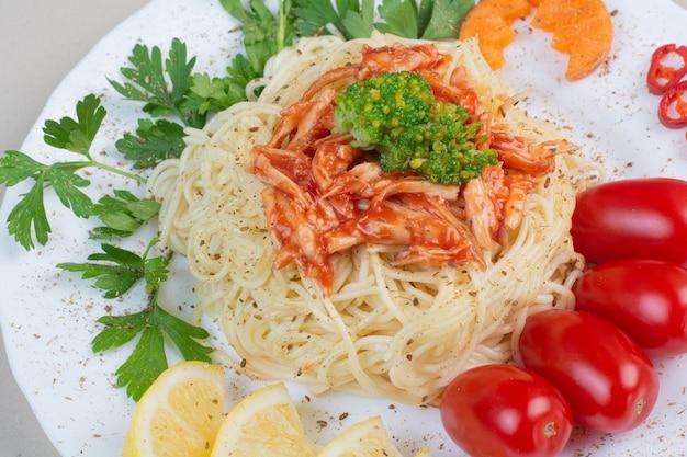 Вкусные спагетти с курицей и овощами на белой тарелке