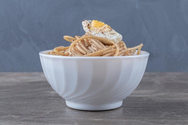 Вкусные спагетти с яйцом в белой миске.