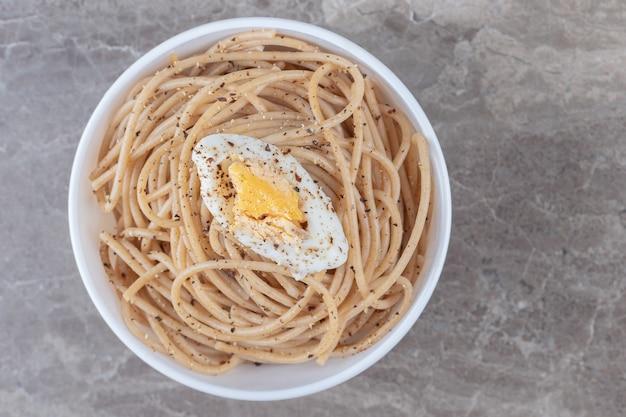 Spaghetti saporiti con l'uovo in ciotola bianca.