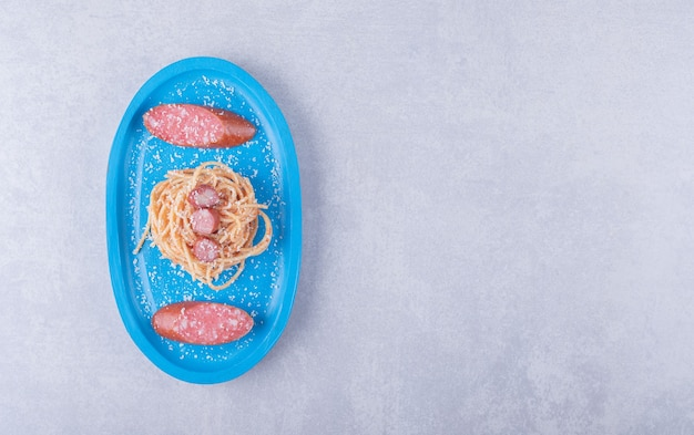 Tasty spaghetti with sausages on blue plate.