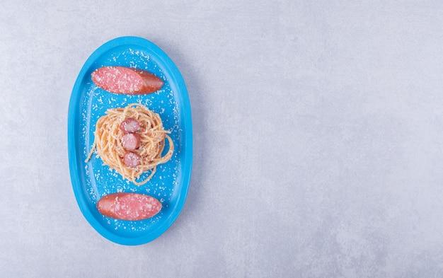 Вкусные спагетти с сосисками на синей тарелке.