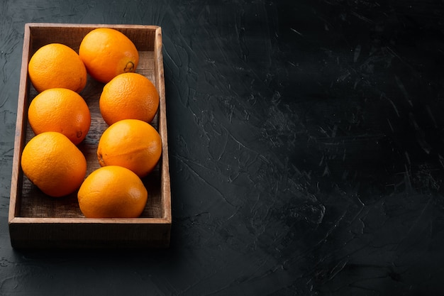 Tasty spanish oranges freshly collected set, in wooden box, on black stone table
