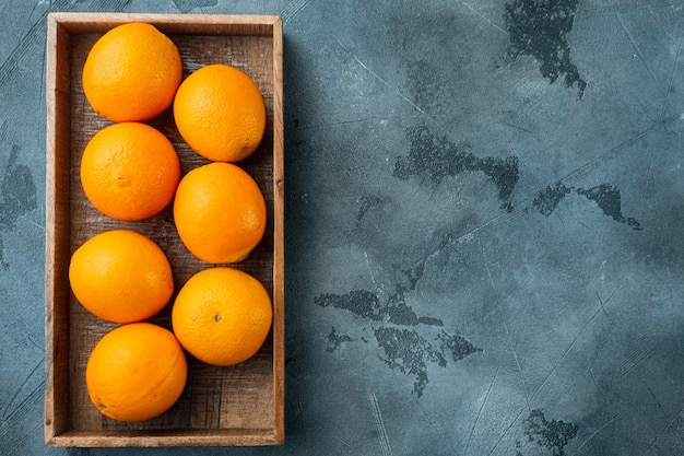 Tasty spanish oranges freshly collected set, in wooden box, on gray stone table, top view flat lay