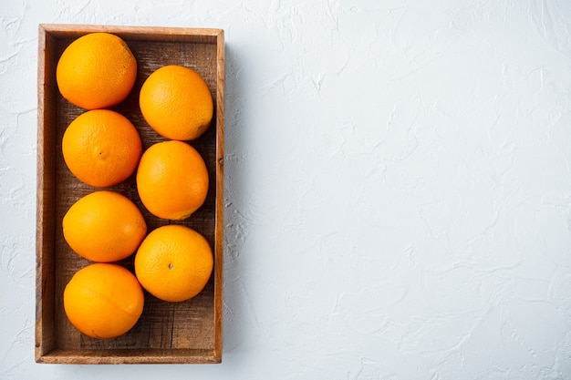 Tasty spanish oranges freshly collected set, in wooden box, on white stone table, top view flat lay