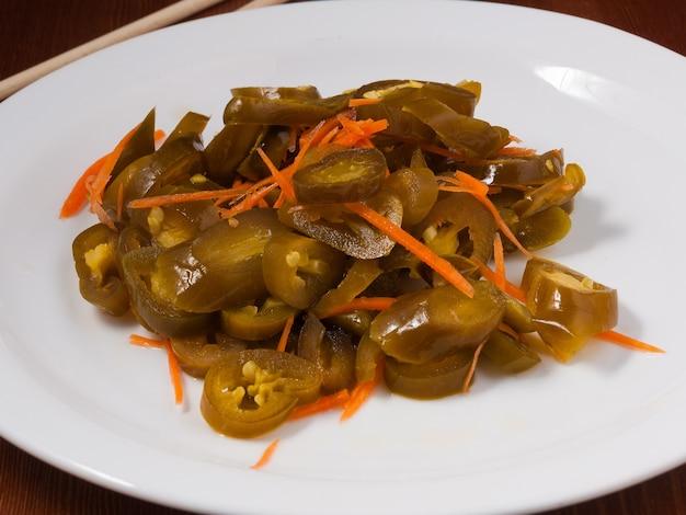 Вкусный пряный маринованный корейский халапеньо на белой тарелке