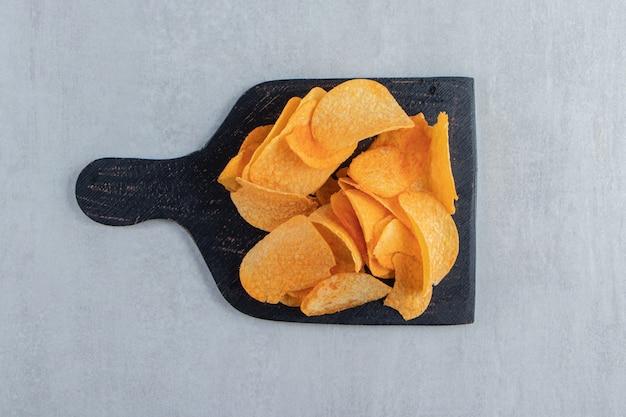 Вкусные пряные картофельные чипсы на черной разделочной доске.