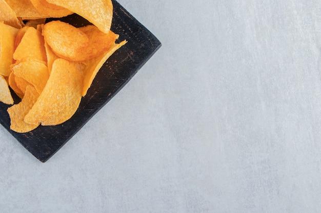 黒のまな板に美味しいスパイシーなポテトチップス。