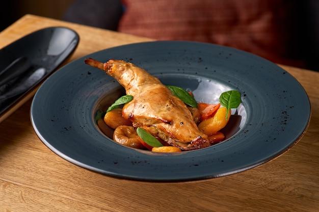 Вкусное острое тушеное мясо из кролика в томатном соусе с белым вином и зеленью крупным планом на столе, сервировка в ресторане