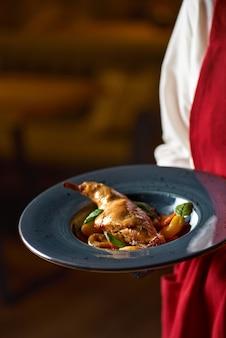 Вкусное острое рагу из кролика в томатном соусе с белым вином и зеленью на тарелке в ресторане в руках официантки.