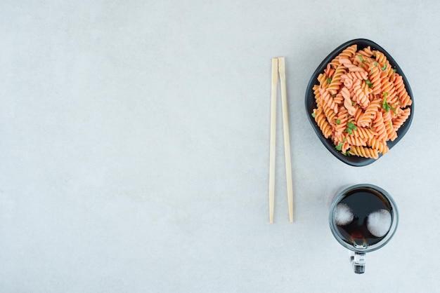 Вкусные спиральные макароны с холодным чаем и палочками для еды.