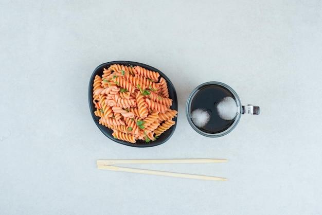 Gustosi maccheroni a spirale con tè freddo e bacchette.