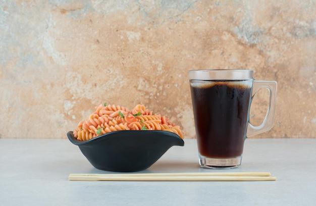 Tasty spiral macaroni with iced tea and chopsticks.