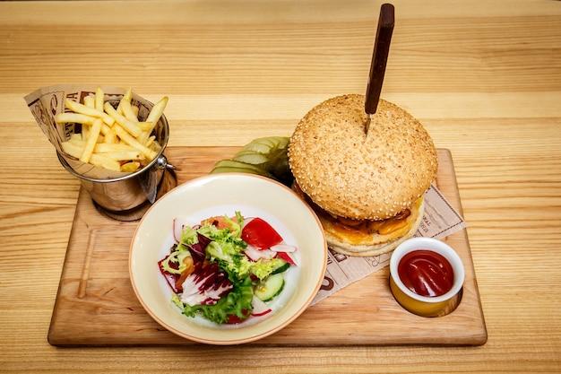 Вкусный стейк-бургер с ломтиками ветчины на деревянной решетке с картофелем фри, овощами и соусом для макания.