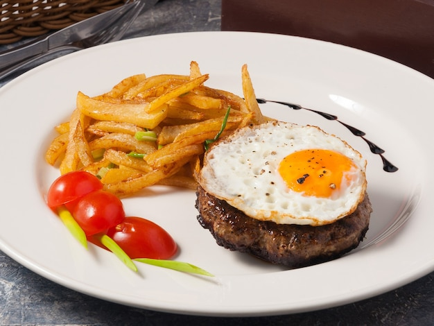 Вкусный стейк с яйцом и картофелем в домашних условиях на белой тарелке