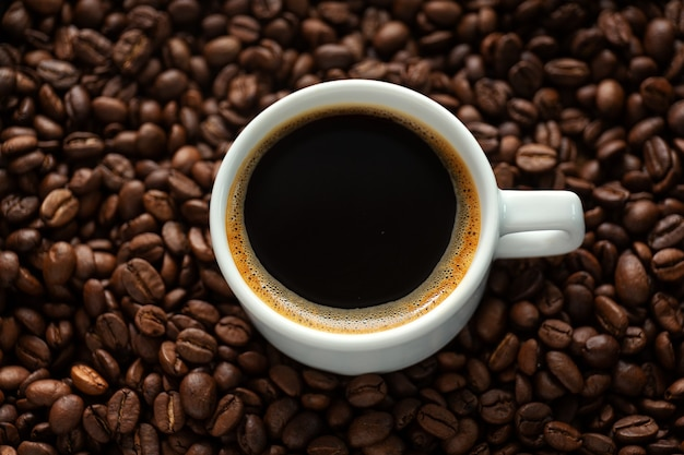 Tasty steaming espresso in cup with coffee beans. closeup