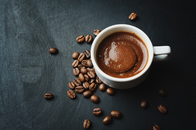 Tasty steaming espresso in cup with coffee beans.