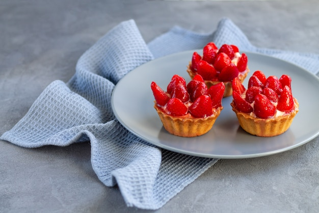 Tasty strawberry cakes on gray plate and linen napkin on stone background
