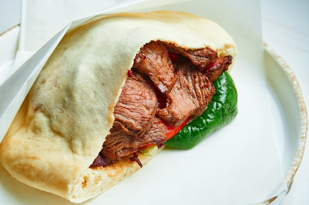 Tasty street food - pita with beef, spinach and tomatoes in parchment on a white ceramic plate on a marble surface.. greek cuisine. close up
