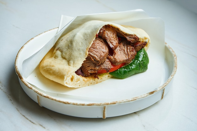 Tasty street food - pita with beef, spinach and tomatoes in parchment on a white ceramic plate on a marble surface.. greek cuisine. close up Premium Photo