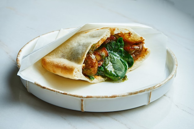 Tasty street food - pita with hummus and mushrooms, spinach and tomatoes in parchment on a white ceramic plate on a marble surface. greek cuisine. close up