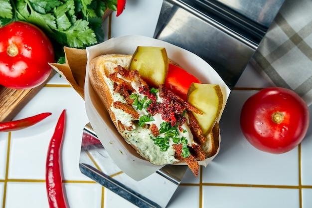 Вкусная уличная еда - лаваш с помидорами, луком и соусом, бургер из говядины на белом столе. греческая кухня крупным планом зрения.