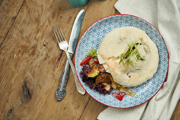 Tasty street food - pita with tomatoes, cucumbers in blue blate on wooden surface. greek cuisine. close up view. shwarma
