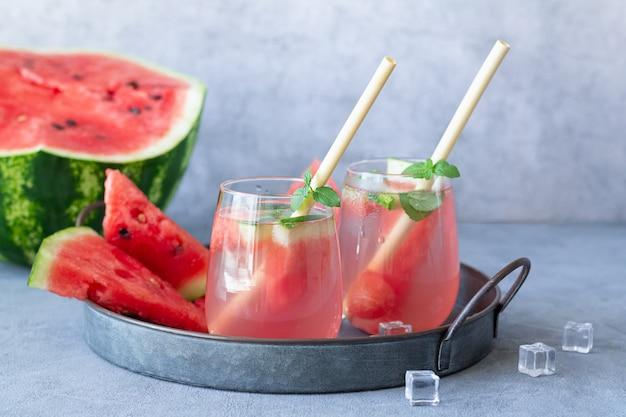 Tasty summer watermelon lemonade in two glasses on stone table