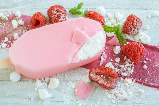 Tasty sundae in pink chocolate and raspberries
