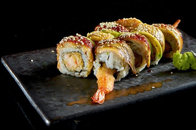 Вкусный суши-ролл с креветками темпура, авокадо и угрем на тарелке с васаби и имбирем