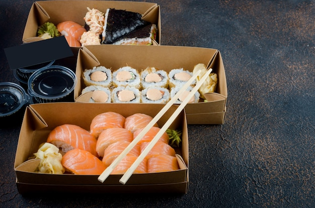 Tasty sushi rolls in disposable kraft paper boxes, sauces on dark table