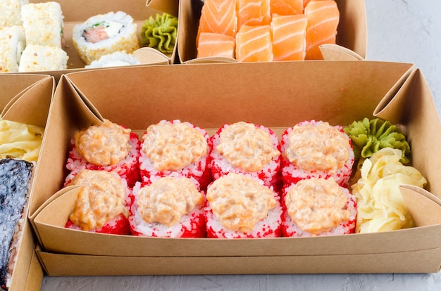 Tasty sushi rolls in disposable kraft paper boxes