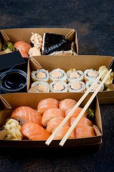 使い捨てクラフト紙箱に入ったおいしい巻き寿司、暗いテーブルのソース