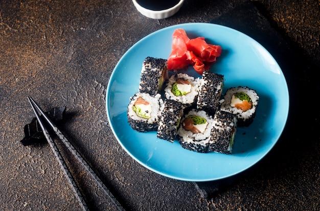 맛있는 스시 롤 검은 젓가락, 생강, 와사비 어두운 배경에 파란색 접시에 검은 참깨에 설정합니다. 스시 메뉴. 배달 서비스 일식.