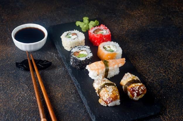 어두운 테이블에 소스, 젓가락, 생강, 와사비와 함께 검은 접시에 맛있는 스시 롤 세트. 스시 메뉴. 배달 서비스 일식. 모듬 스시, 롤, 군함, 초밥.