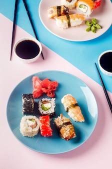 Вкусные суши-роллы на синей тарелке с соусами, палочками для еды, имбирем и васаби на фоне.