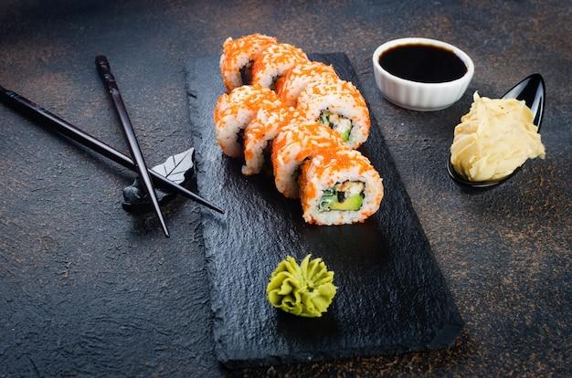 Вкусные суши-роллы на каменной тарелке с соусами