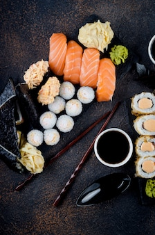 Tasty sushi rolls set on stone plate with sauces, chopsticks, ginger and wasabi