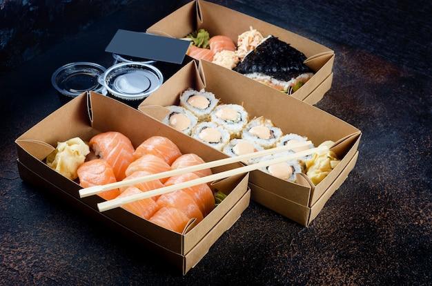 Вкусные суши-роллы с соусами, палочками для еды, имбирем на столе