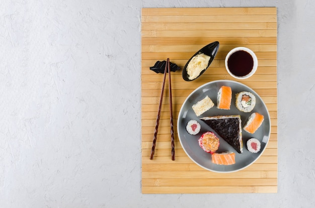 Tasty sushi rolls set with sauces, chopsticks, ginger on table. delivery service japanese food