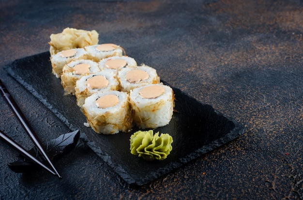Tasty sushi rolls set with sauces, chopsticks, ginger on table