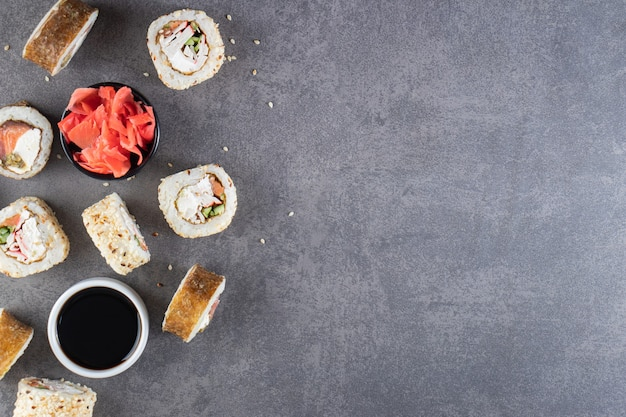 石の背景にマグロを乗せた美味しい巻き寿司。