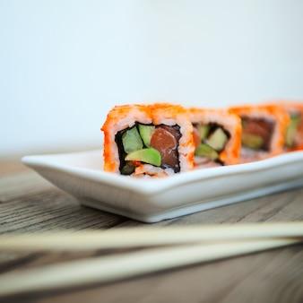 Tasty sushi with chopsticks