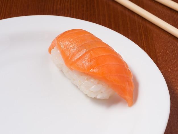 白いプレートにサーモンのおいしい寿司をクローズアップ