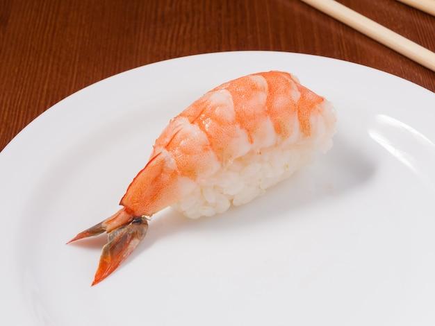 白いプレートにエビのおいしい寿司をクローズアップ