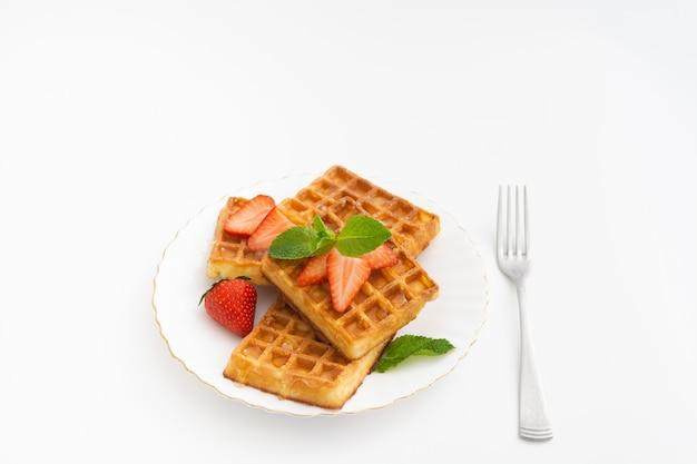 접시에 딸기 장식으로 맛있는 달콤한 벨기에 와플