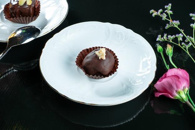 Tasty sweet chocolate candy on a white saucer on dark. tea dessert. food photo