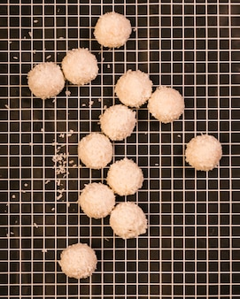 Tasty sweet coconut balls on checkered textile